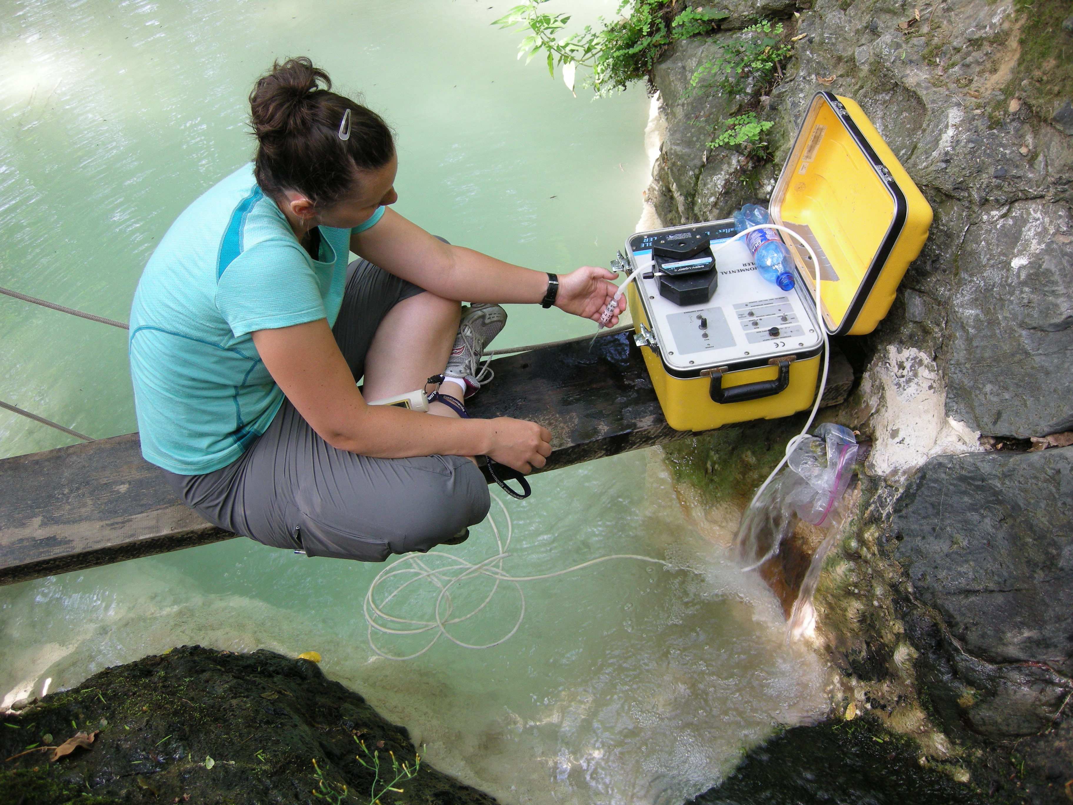 Katrina Twing (East Carolina University) samples pH 12 serpentinite springs at the Liguria Ophiolite, Italy. The pump and tubing visible in the photo are used to collect subsurface fluid samples for chemistry and DNA sequencing. Photo: Billy Brazelton (ECU).
